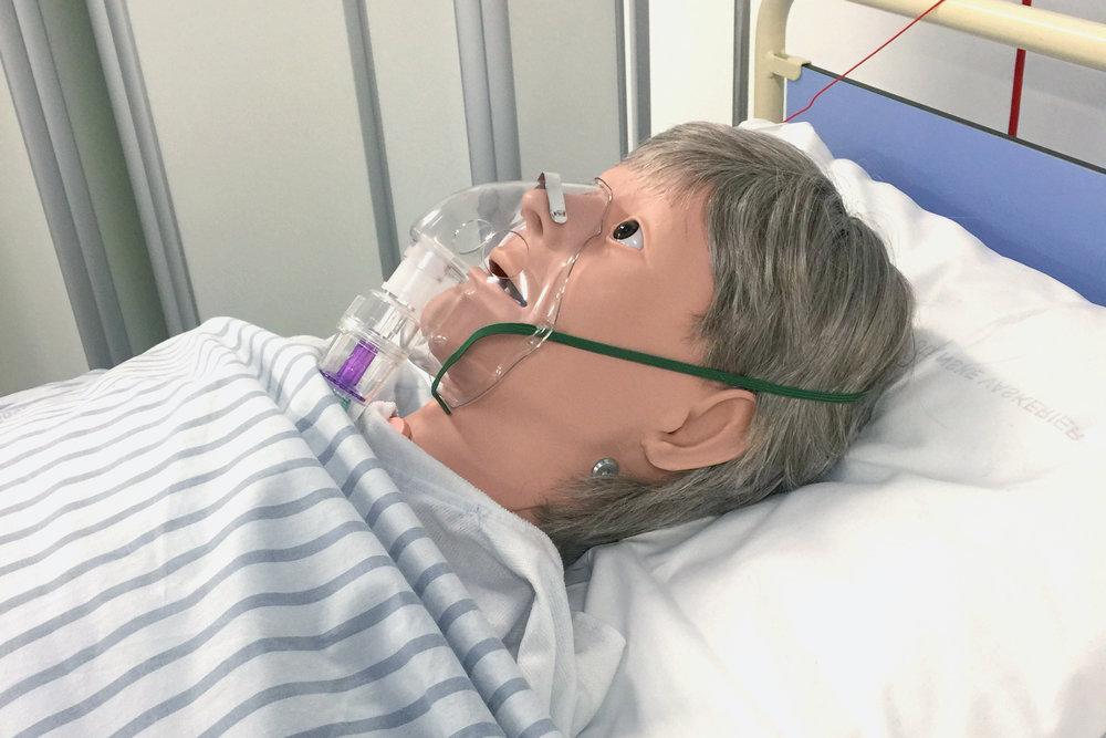 En simulationsdukke ligger i en sygeseng med iltmaske over mund og næse.
