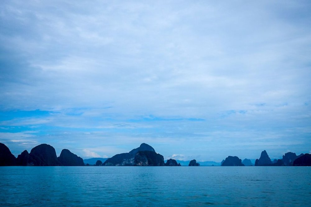 As the sun sets in Thailand the emerald greens give way to a sea of cool, glassy blues.