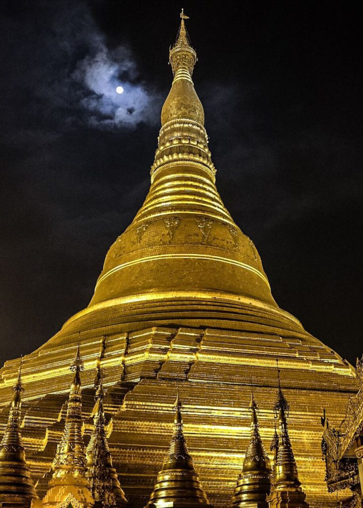 The gilded peaks of Yangon's Shwedagon Pagoda reaching up to a full moon.