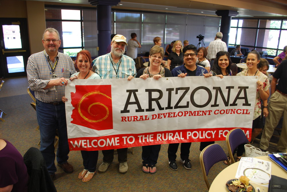 Past Rural Policy Forum attendees gather for a group photo with the Arizona Rural Development Council Banner.
