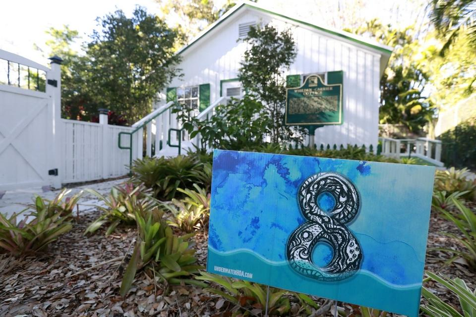 """PINECREST, Fla. -- A yard sign stating that the area is eight feet above sea level is shown in front of artist Xavier Cortada's studio in Pinecrest. Cortada created an """"Underwater Homeowner's Association,"""" a kind of community installation to promote awareness about rising sea levels. Participating homeowners get signs in their yards noting how many feet about sea level they stand, and they are holding real meetings, like any other homeowner's association, to discuss how their suburban community can prepare for the effects of climate change. [AP Photo/Wilfredo Lee]"""