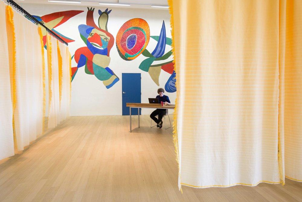 Arnon Grunberg aan net werk. Voor de Karel Appel muurschildering. De oranje gordijnen - op eigenlijk meer een rijpe papaya kleur - geven een beetje richting aan een verder heel open zaal (4 verschillende ingangen !) (foto : Maarten Nauw)