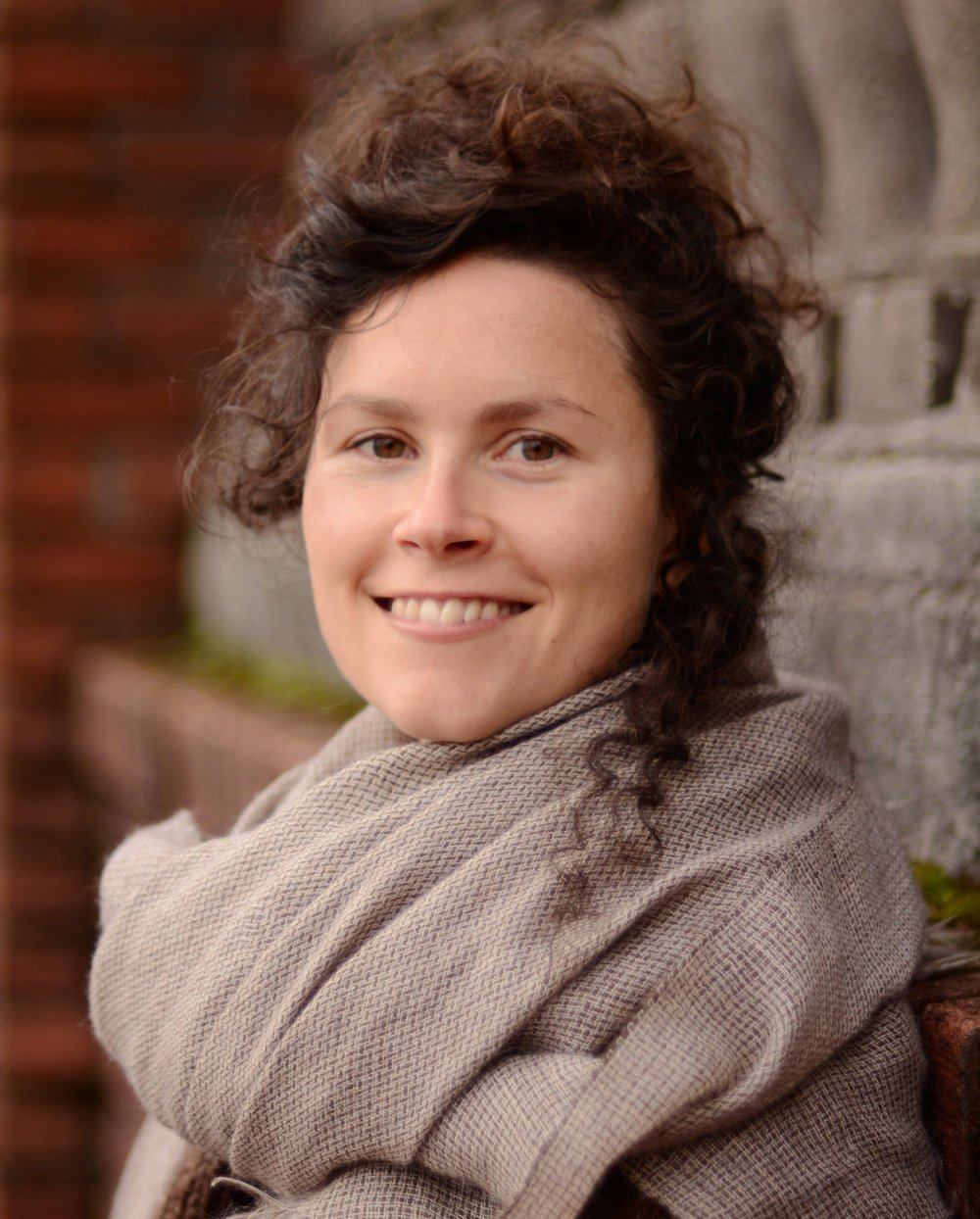 Smiling woman with dark curly hair and oversized grey scarf