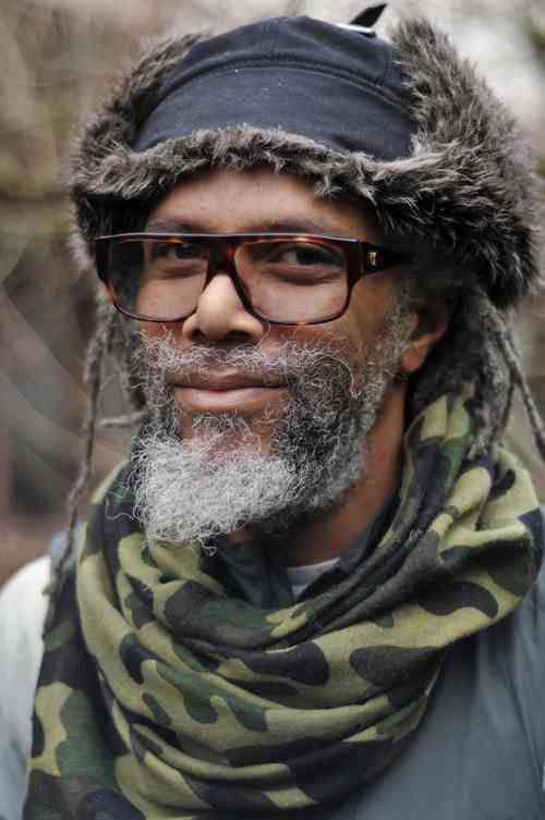 Man with grey dreadlocks wears glasses, a hat, and a camo print scarf