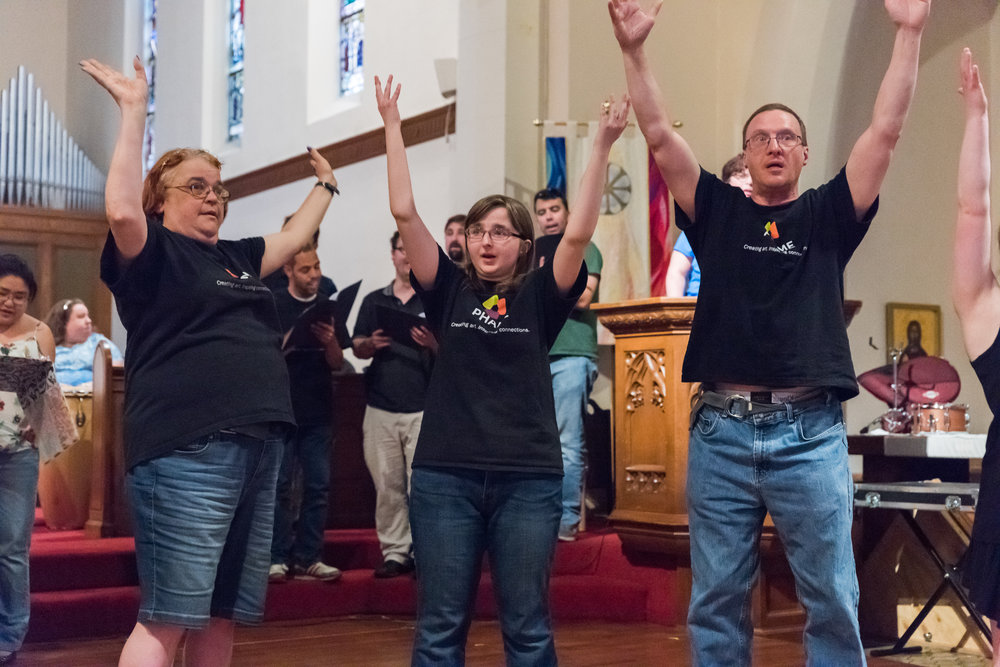 Three people wearing black PHAME t-shirts stand in front of a group of singers and raise their arms, they are possibly singing