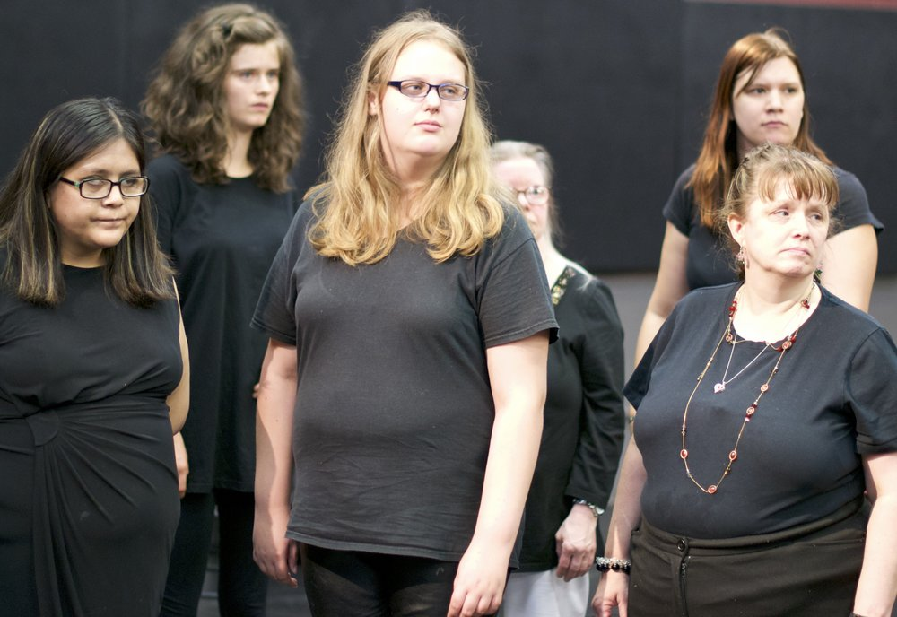 Group of women dressed in black look off to the side