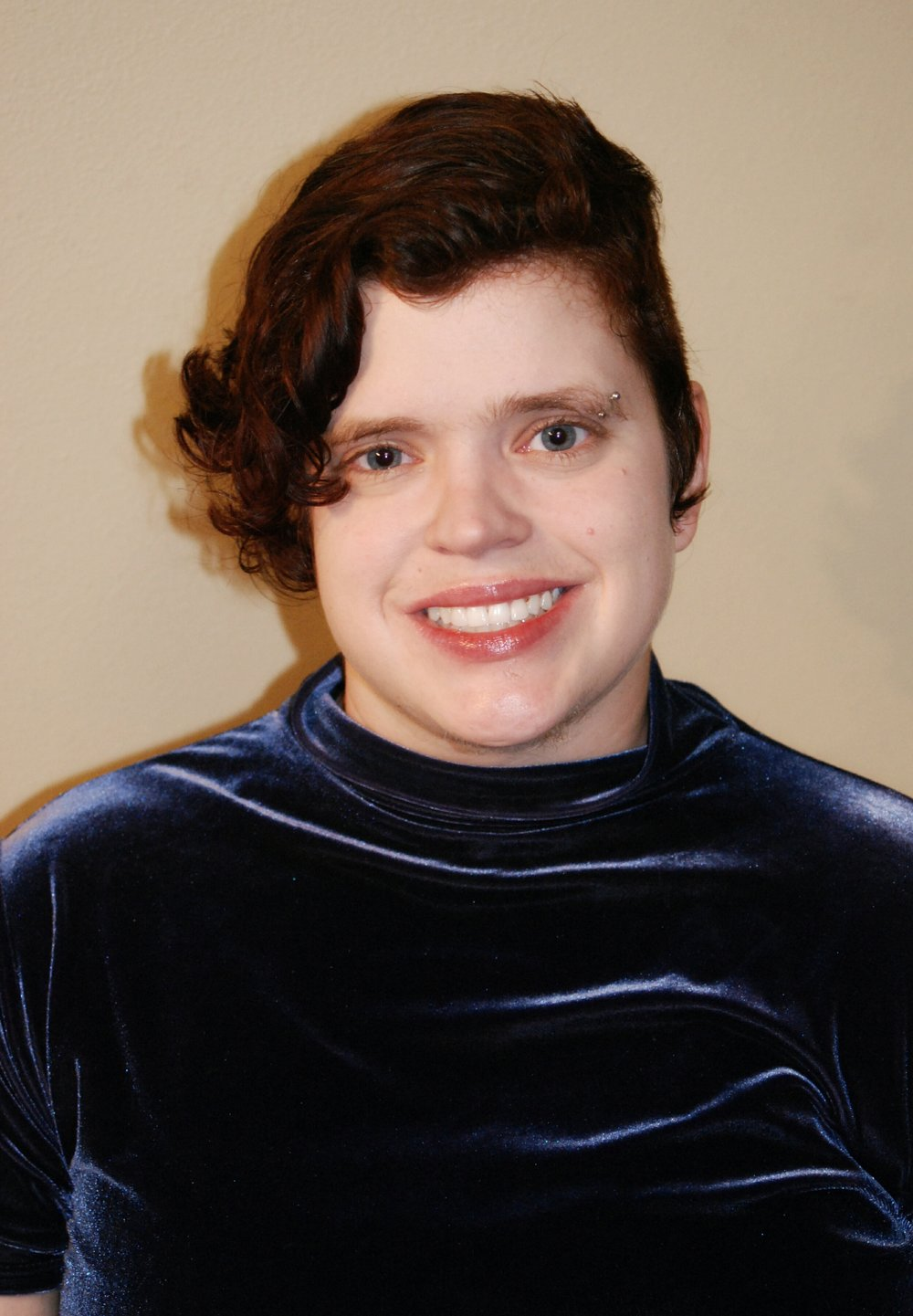 Smiling person with short curly hair and a blue shiny shirt.
