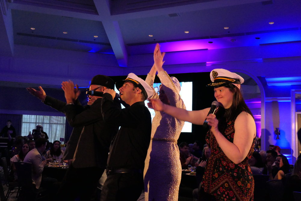 Group of five people dancing and signing, two with sailor hats.