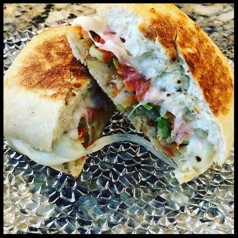 Veggie grilled cheese on ciabatta  - Grill sliced brussel sprouts and onions with minced garlic and olive oil until lightly brownedSlice and grill tomatoes for 2 minutes on each side on medium-high heat Remove from heat and place (the inside of) halved ciabatta on an oiled (olive oil or ghee) griddle (or frying pan) until outside is brownedFlip to outside and put ingredients inside adding cheese of your choice (horseradish cheddar is my favorite) and grill until browned flipping once to brown other outer side.