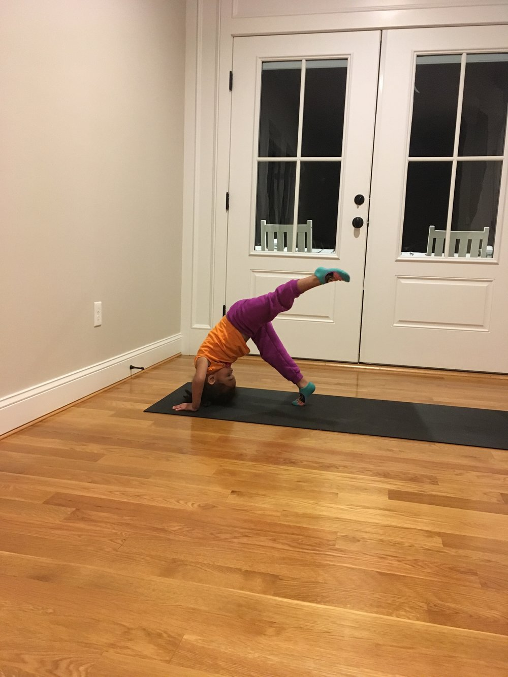 child doing yoga pose at home