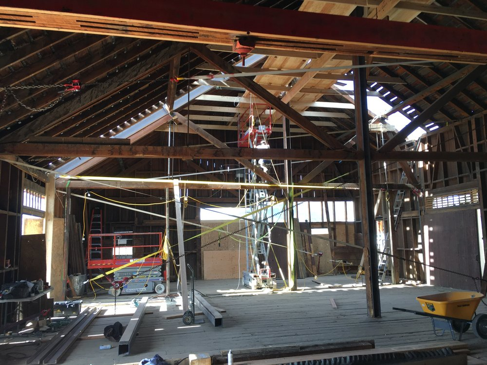 "The depot was ready to fall over when it was purchased in May 2017. 3 of the 5 trusses were no longer functional. The solution? To sandwich existing timbers with steel. This allowed the original framing to remain exposed while bringing the walls close back to plumb. Both East and west walls were trying to fall outward and were 2.5"" to 3"" off plumb. Cam straps were used to pull the building back in line as steel was inserted."