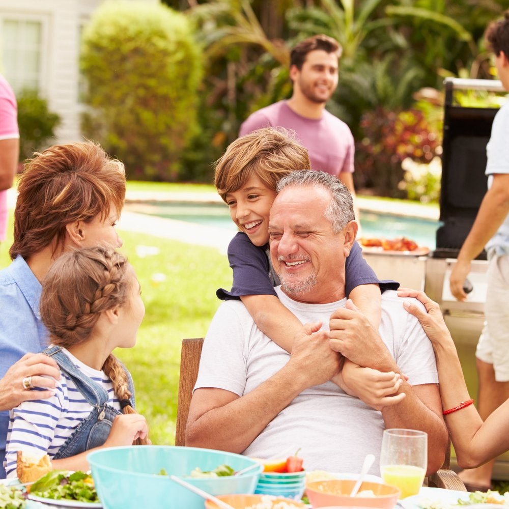 multi-generation-family-enjoying-meal-in-garden-PHLFX97.jpg