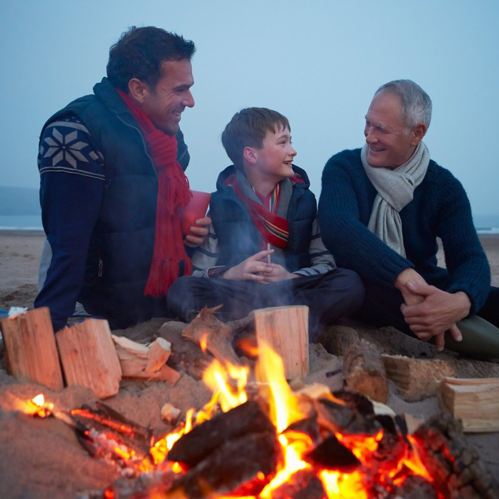 multi-generation-family-sitting-by-fire-on-winter-P7ZJCSD.jpg