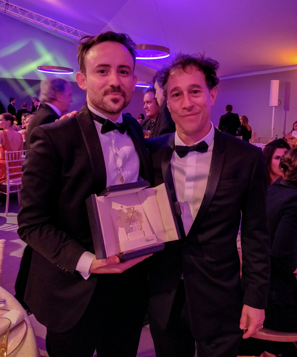 L-R Charles Williams holding his Palme d'Or Prize with President of the Cannes Short Film Jury, Bertrand Bonello - courtesy of the artist