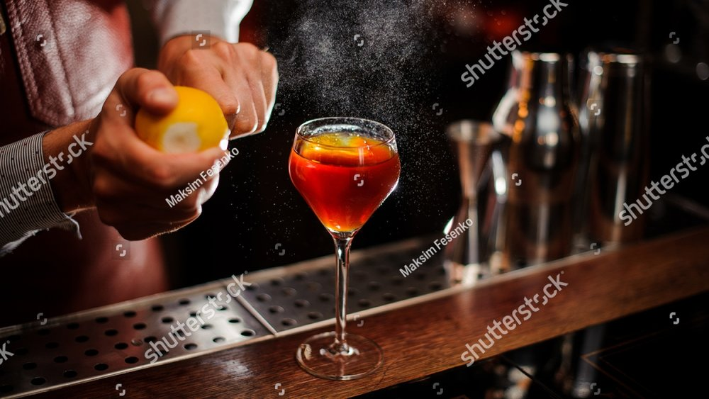 stock-photo-bartender-is-adding-lemon-zest-to-the-red-cocktail-at-bar-counter-selective-focus-697322692.jpg