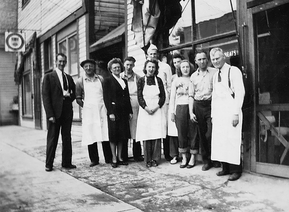 Dick Askew, 2nd from left with employees and family members: Mac Drage, Gwen Drage, Don, Marjorie, David, Marion and Doreen Askew, Mike Bodner and Fred Lee in front of the alexander location in the late 40's.