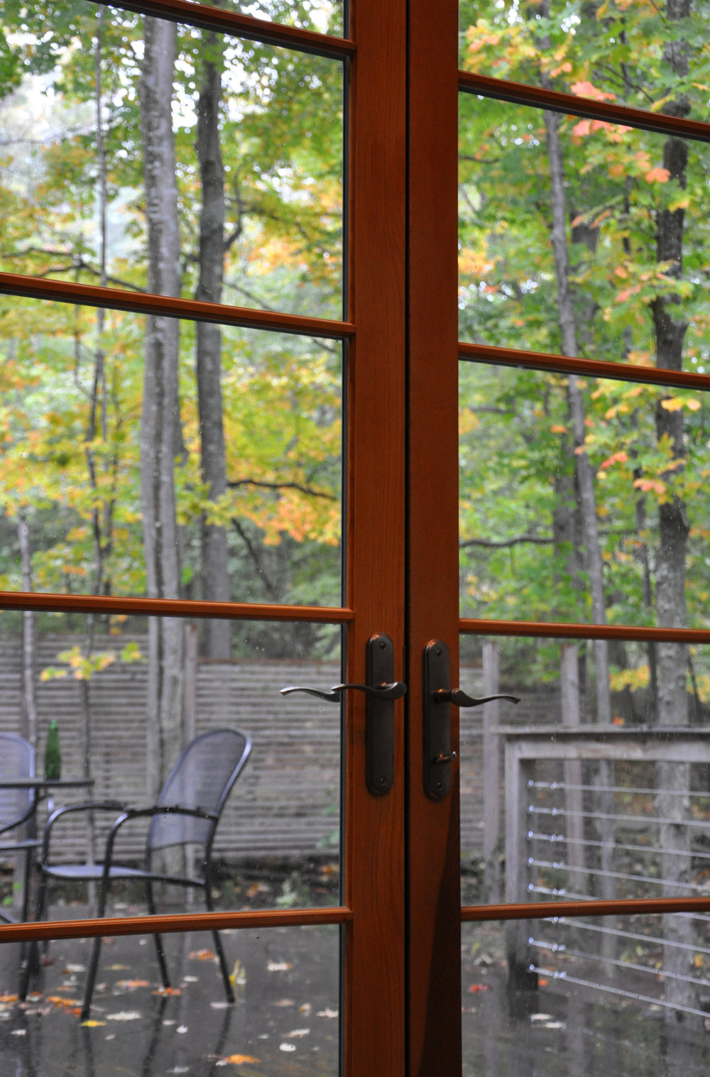 view through wooden french doors to pack porch deck, autumn leaves, outdoor seating