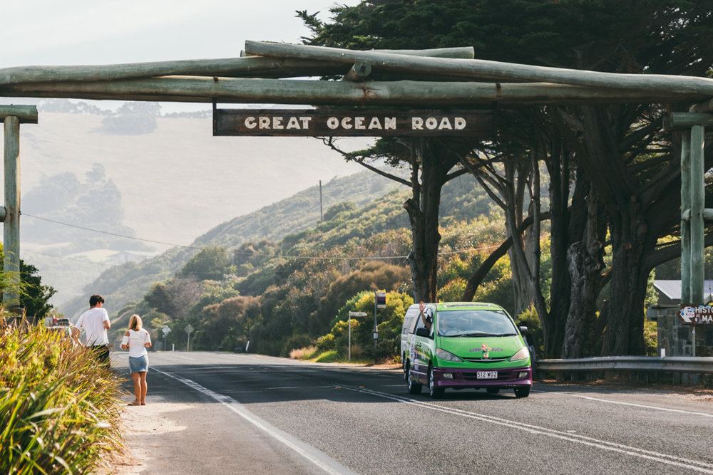 A jucy rentals van drives under the Great Ocean Road memorial arch, Victoria, Australia