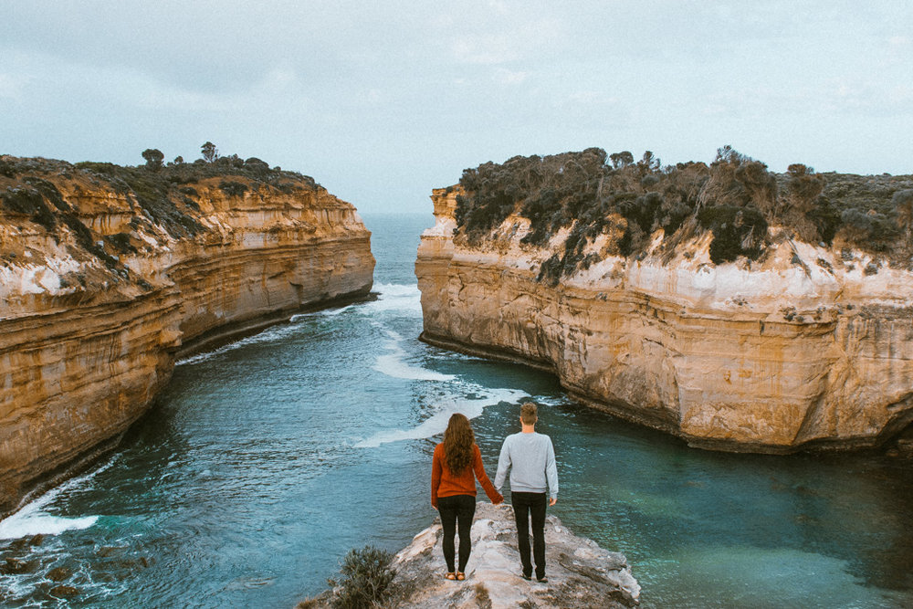 A man and woman overlook Loch Ard Gorge, Port Campbell National Park, Victoria