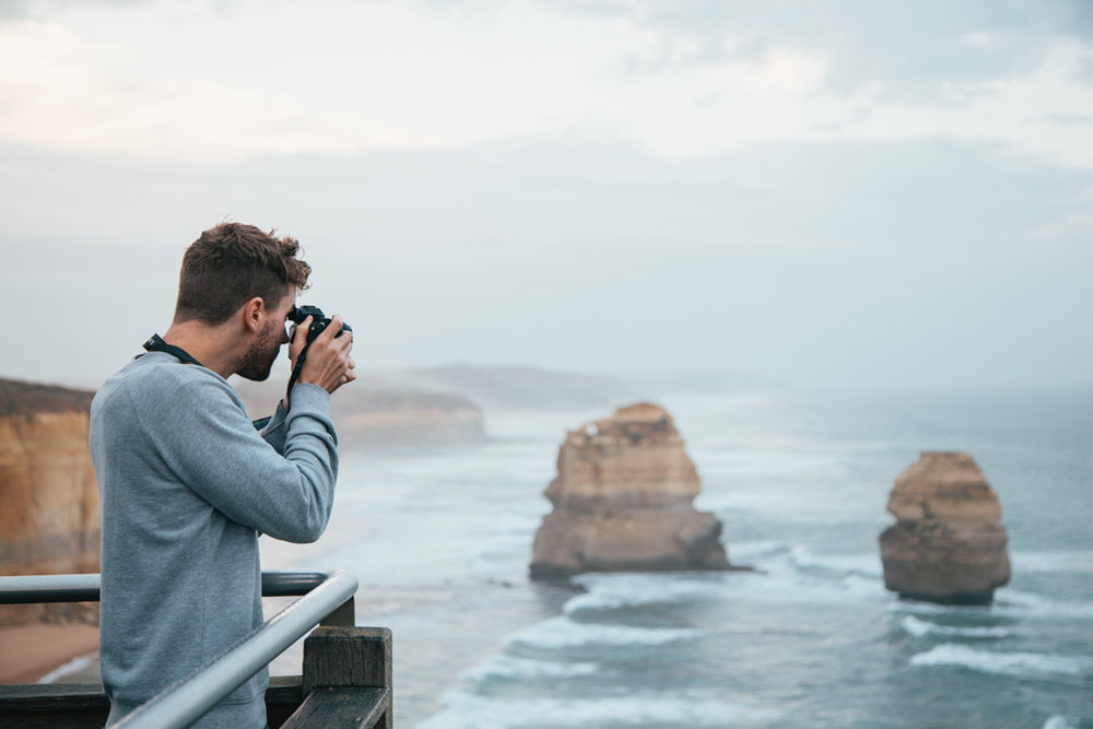 A man photographs the 12 Apostles, Port Campbell National Park, Victoria, Australia