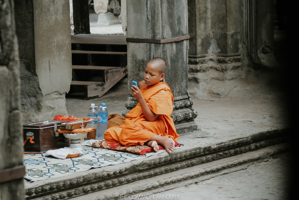 Cambodia photo diary monk plays on his phone at angkor wat