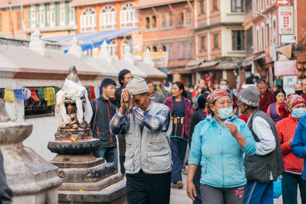 The old man pauses to pray at Boudhanath Stupa.jpg