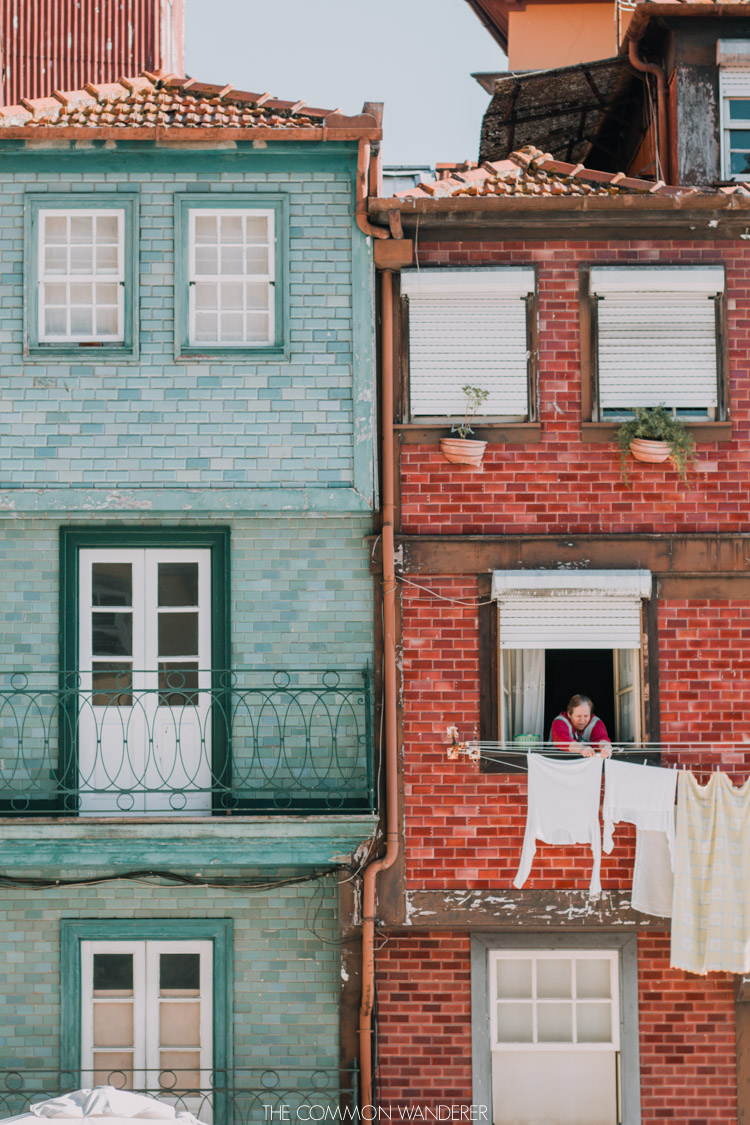A lady hangs out washing from the colourful buildings of Porto's Ribeira district