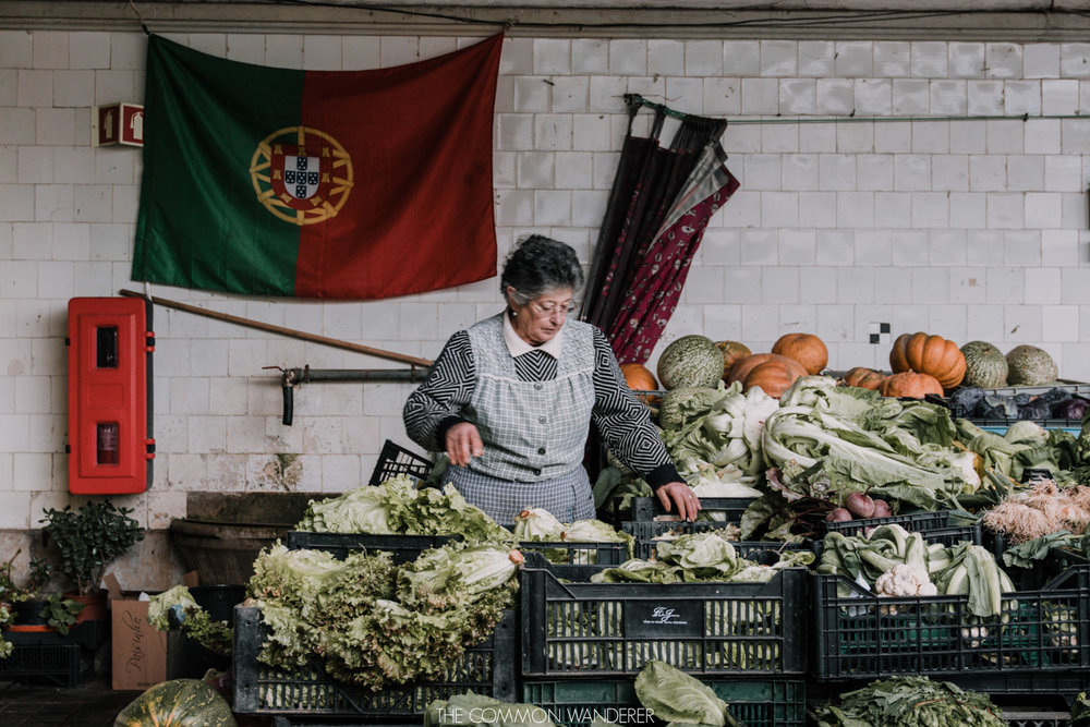 A lady sorts vegetables inside the Mercado do Bolhao in Porto, things to see in Porto
