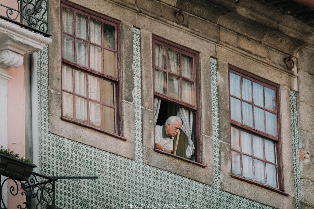 Man looks out his Porto window to the Ribeira district below - Porto photo diary