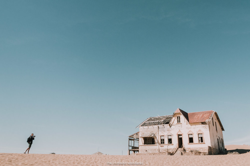 A man photographing an abandoned house in Kolmanskop, Namibia