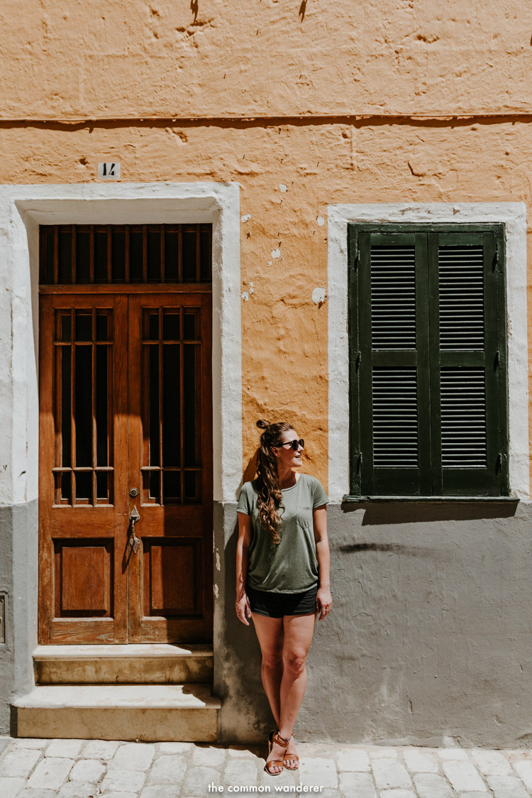 a woman stands in front of a colourful wall, Ciutadella, Menorca