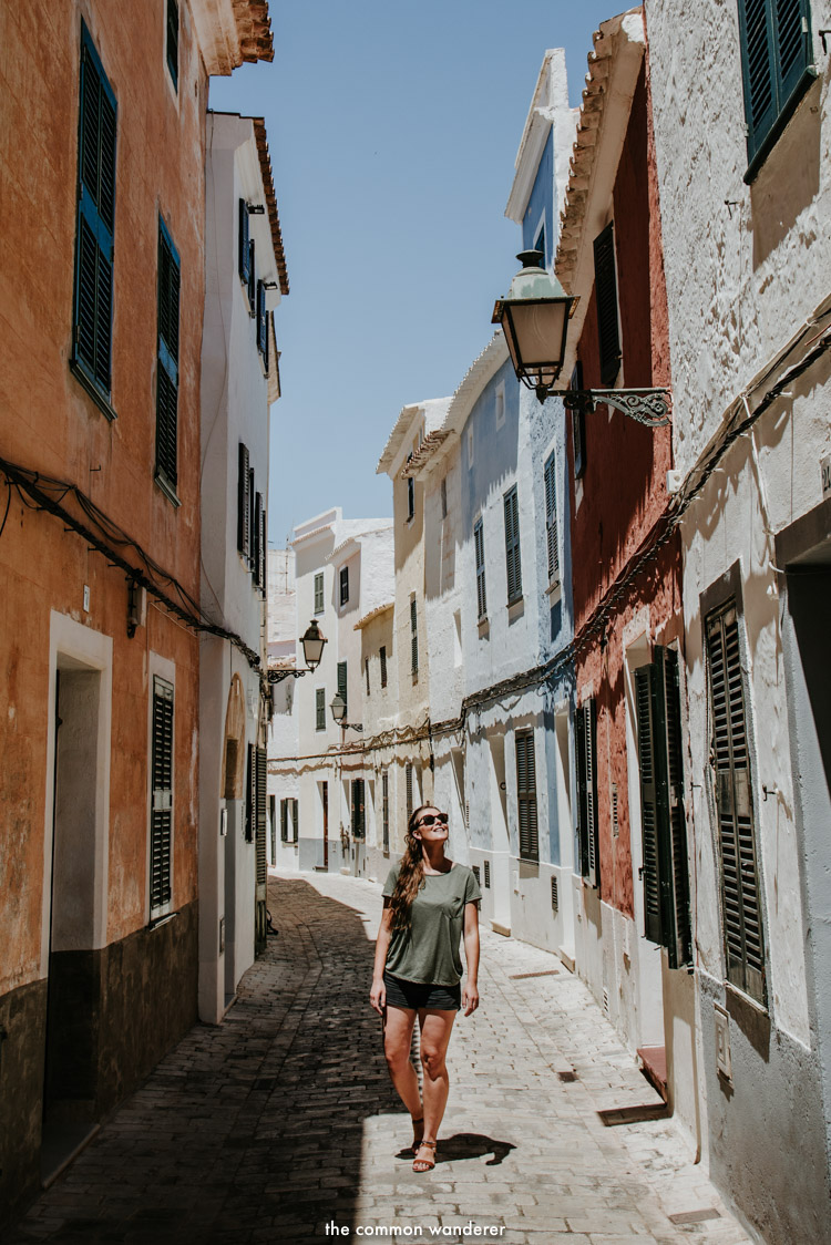 A woman walks down the colourful streets of Ciutadella, Menorca