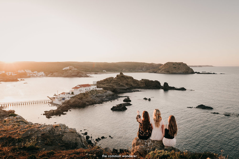 Three women watch the sun set in Menorca, Spain.