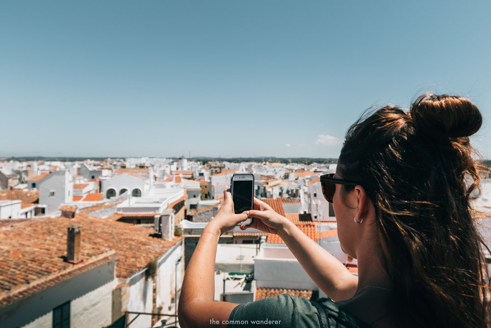 A woman takes a photo on her smartphone overlooking Ciutdella, Menorca