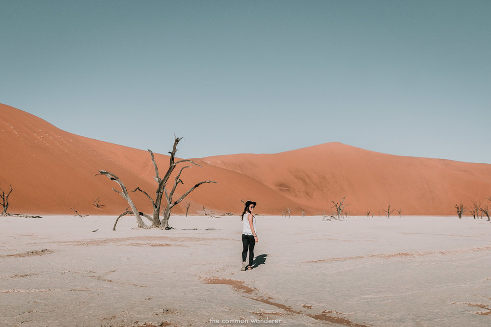 A woman walking amongst the trees in Deadvlei - Sossusvlei, Namibia