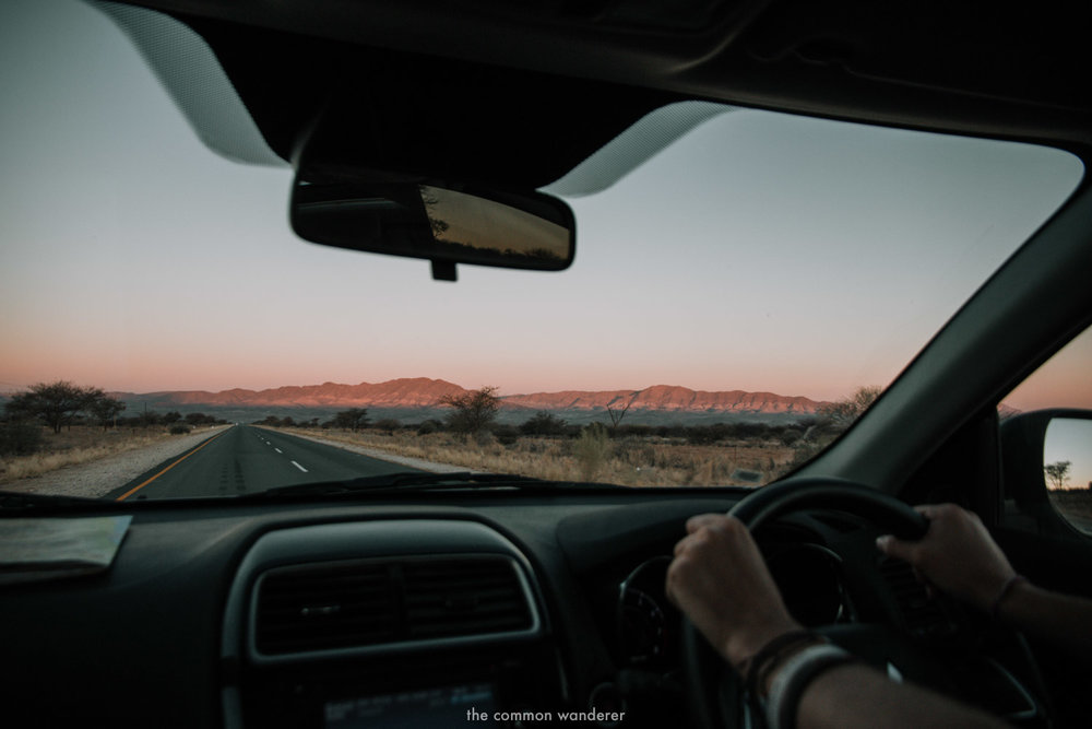 Driving at dusk along a long road in Namibia