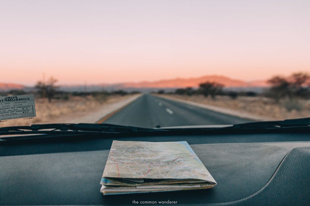 A road map on the dashboard of a car, sun setting in the background - Namibia