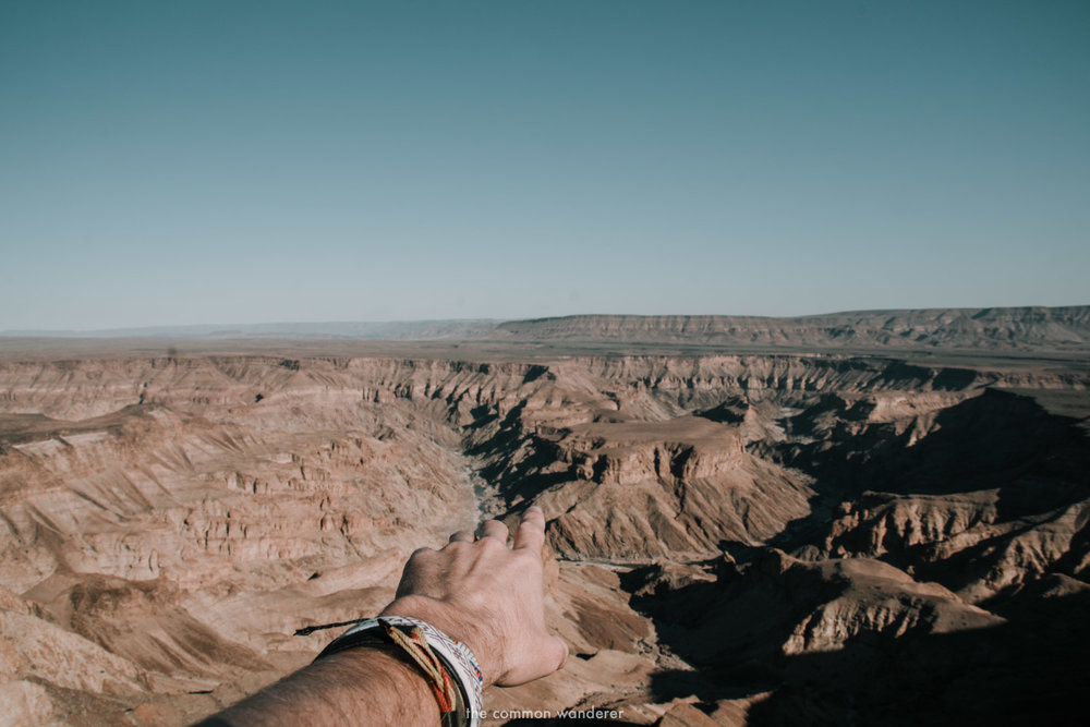 A man points into Fish River Canyon, Namibia