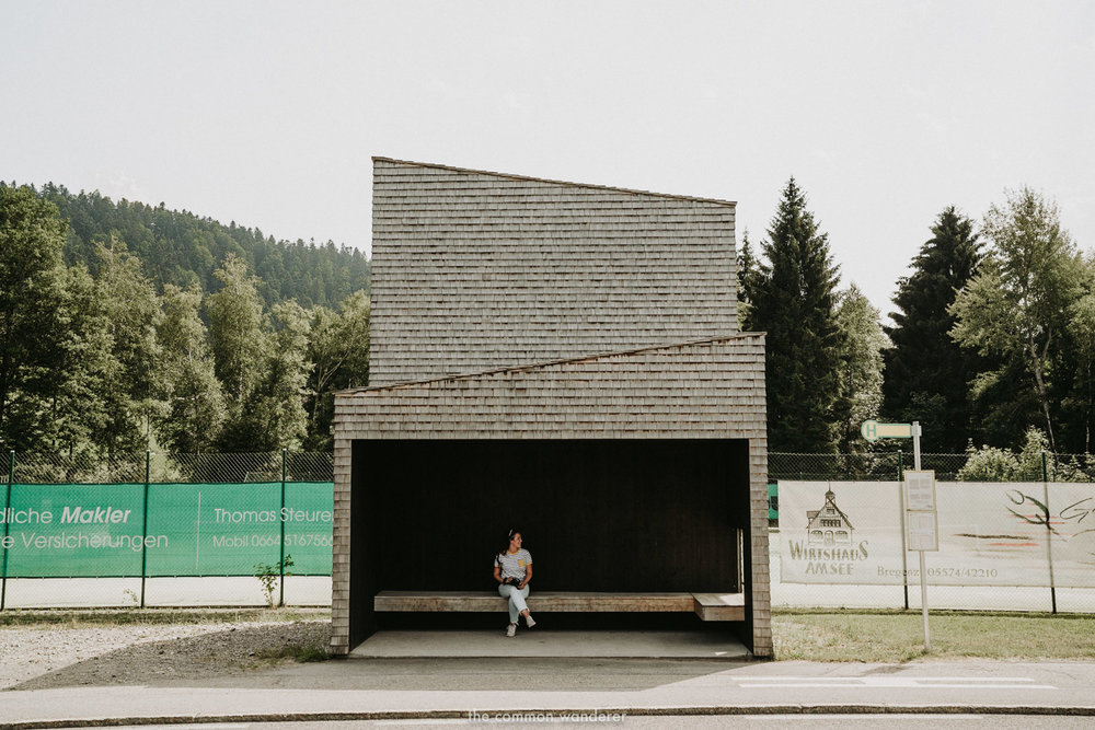 woman sitting in front of Bus:Stop Krumbach, Vorarlberg