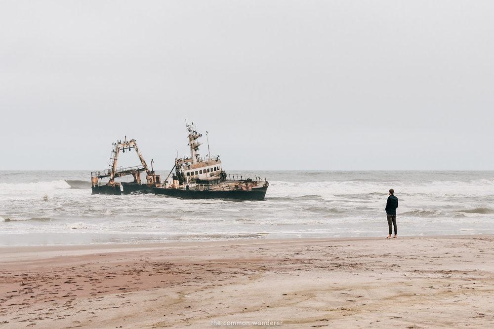 A man overlooks a shipwreck on the Shipwreck Coast, Namibia
