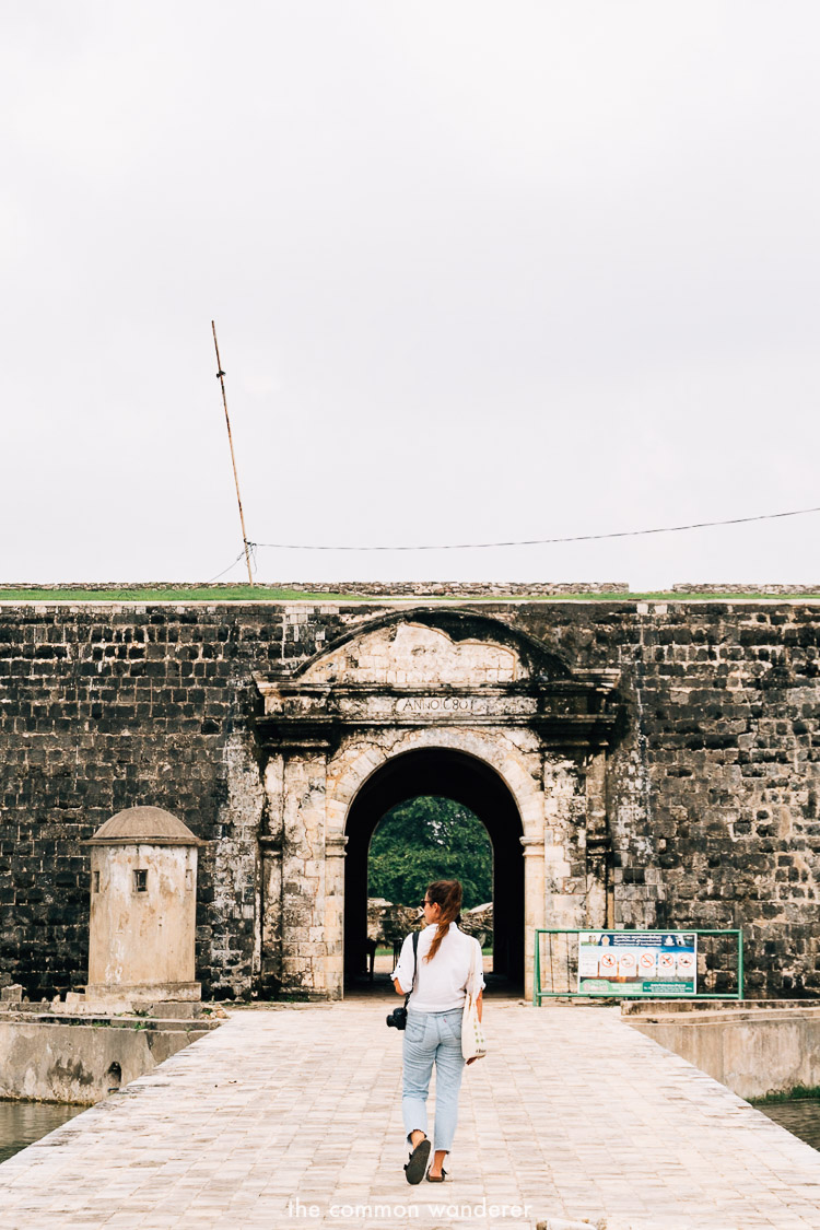 A woman walking into Jaffna Fort, one of the best things to do in Jaffna, Sri Lanka