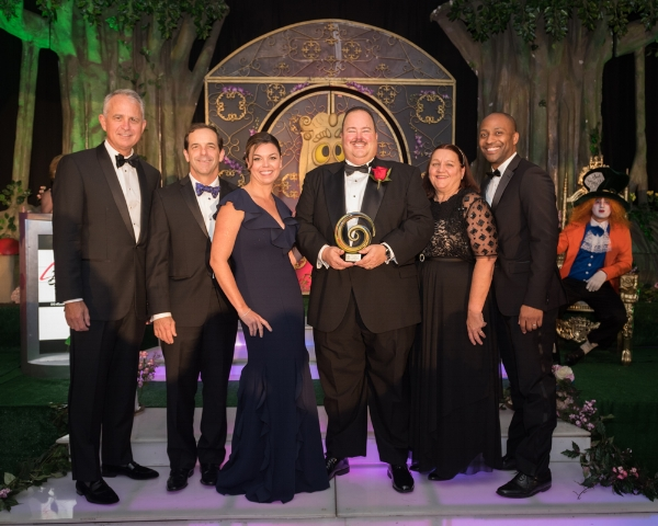 Amaury Piedra accepting his award with Tavistock Development Company executives