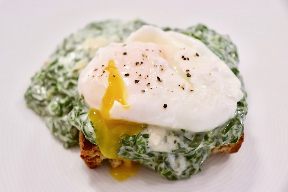 Poached egg on wilted spinach in béchamel sauce on homemade soda bread toast