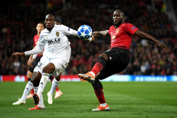 Romelu Lukaku of Manchester United is challenged by Geoffrey Kondogbia of Valencia during the Group H match of the UEFA Champions League between Manchester United and Valencia at Old Trafford on October 2, 2018 in Manchester, United Kingdom.  (Oct. 1, 2018 - Source: Michael Regan/Getty Images Europe)
