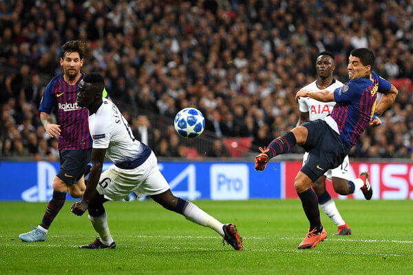 Luis Suarez of Barcelona shoots while under pressure from Davinson Sanchez of Tottenham Hotspur during the Group B match of the UEFA Champions League between Tottenham Hotspur and FC Barcelona at Wembley Stadium on October 3, 2018 in London, United Kingdom.  (Oct. 2, 2018 - Source: Shaun Botterill/Getty Images Europe)