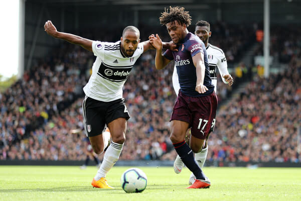 Alex Iwobi of Arsenal battles for possession with Denis Odoi of Fulham during the Premier League match between Fulham FC and Arsenal FC at Craven Cottage on October 7, 2018 in London, United Kingdom.  (Oct. 6, 2018 - Source: Bryn Lennon/Getty Images Europe)