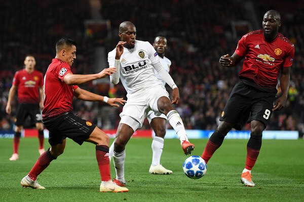 Geoffrey Kondogbia of Valencia is challenged by Alexis Sanchez of Manchester United during the Group H match of the UEFA Champions League between Manchester United and Valencia at Old Trafford on October 2, 2018 in Manchester, United Kingdom.  (Oct. 1, 2018 - Source: Michael Regan/Getty Images Europe)