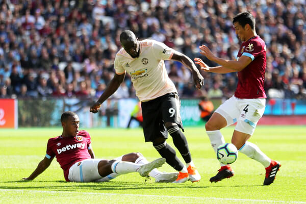 Romelu Lukaku of Manchester United is tackled by Issa Diop (l) and Fabian Balbuena of West Ham United during the Premier League match between West Ham United and Manchester United at London Stadium on September 29, 2018 in London, United Kingdom.  (Sept. 28, 2018 - Source: Warren Little/Getty Images Europe)
