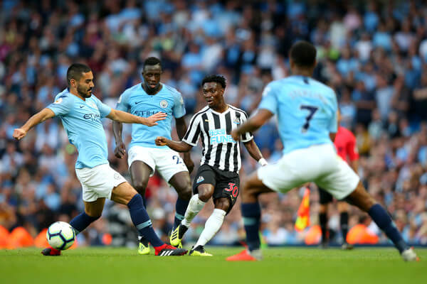 Christian Atsu of Newcastle United is challenged by Ilkay Gundogan of Manchester City and Benjamin Mendy of Manchester City during the Premier League match between Manchester City and Newcastle United at Etihad Stadium on September 1, 2018 in Manchester, United Kingdom.  (Aug. 31, 2018 - Source: Alex Livesey/Getty Images Europe)