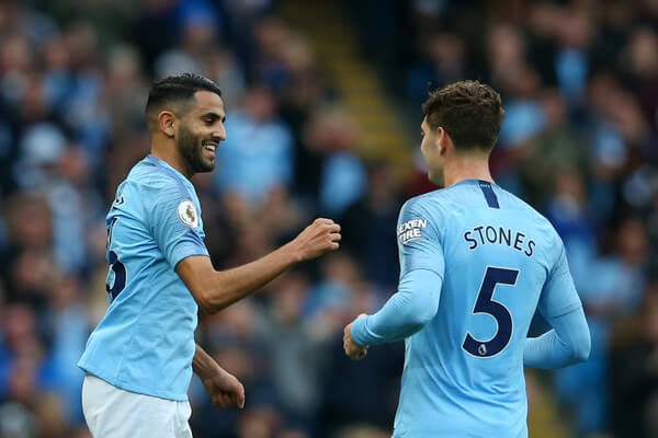 Riyad Mahrez of Manchester City celebrates after scoring his team's fourth goal with John Stones of Manchester City during the Premier League match between Manchester City and Burnley FC at Etihad Stadium on October 20, 2018 in Manchester, United Kingdom.  (Oct. 19, 2018 - Source: Alex Livesey/Getty Images Europe)